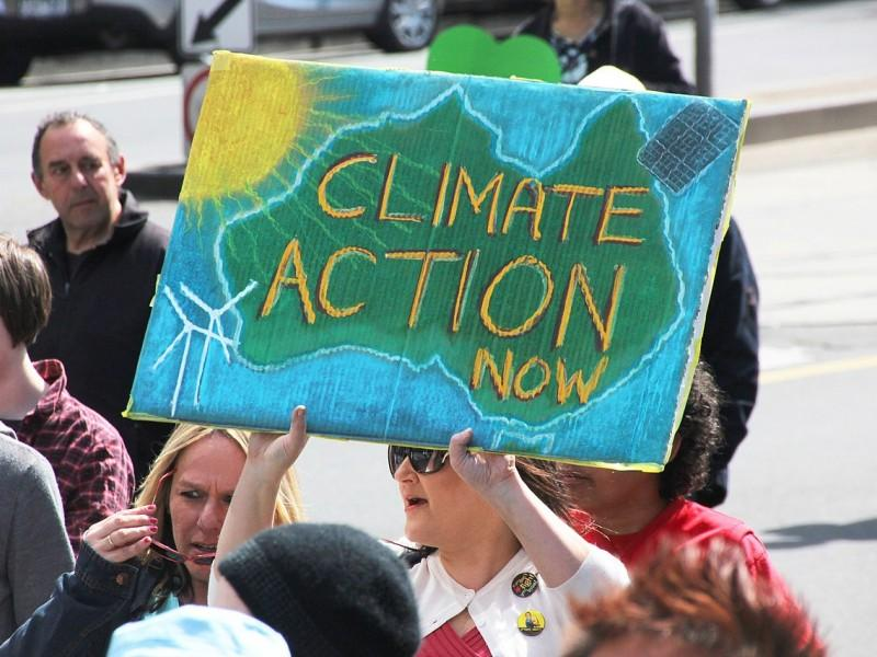 "Photo of an Australian woman holding a protest sign reading, ""Climate Action Now."""