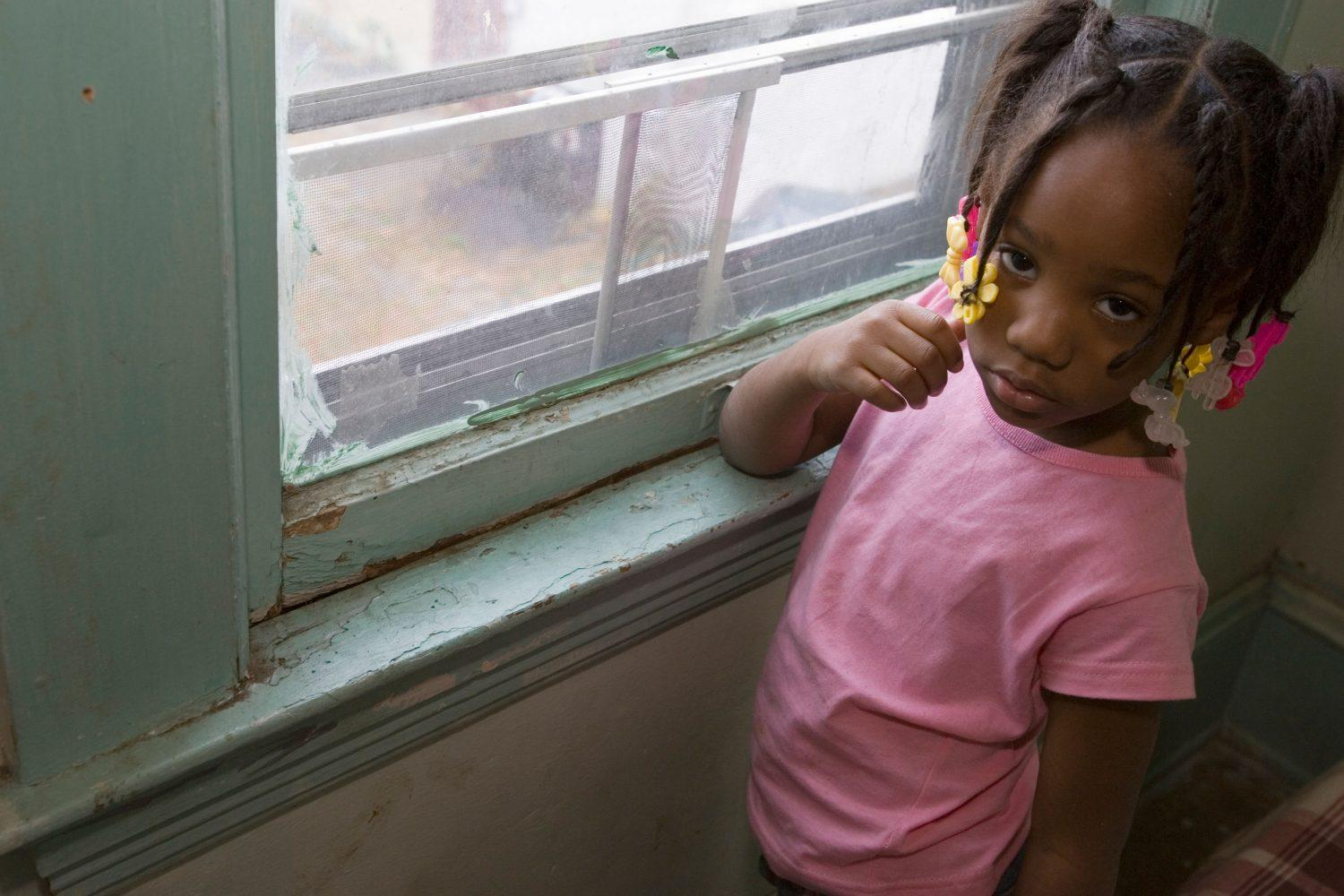 Four-year-old Taharah Abdulhaqq stands by a window in her home, where lead-based paint chips from the wood.