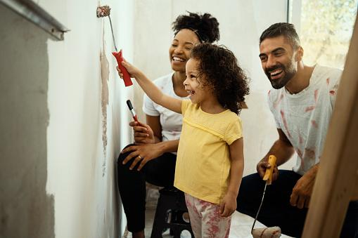 A young family paints a wall in their house.
