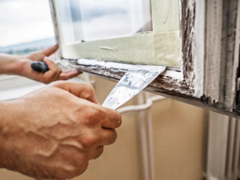 Close-up photo of hands scraping old paint from a window frame.