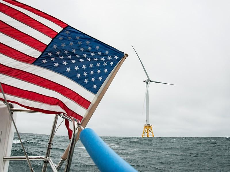 View of a wind turbine off the coast of Block Island, Rhode Island from a boat donned with a waving U.S. flag