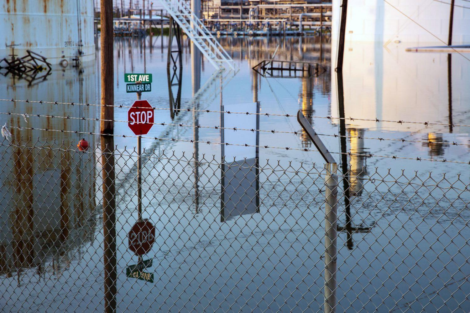 Photo of a stop sign and large storage tanks submerged in water after Hurricane Harvey flooded Motiva's oil refinery in Port Arthur, Texas, in 2017.