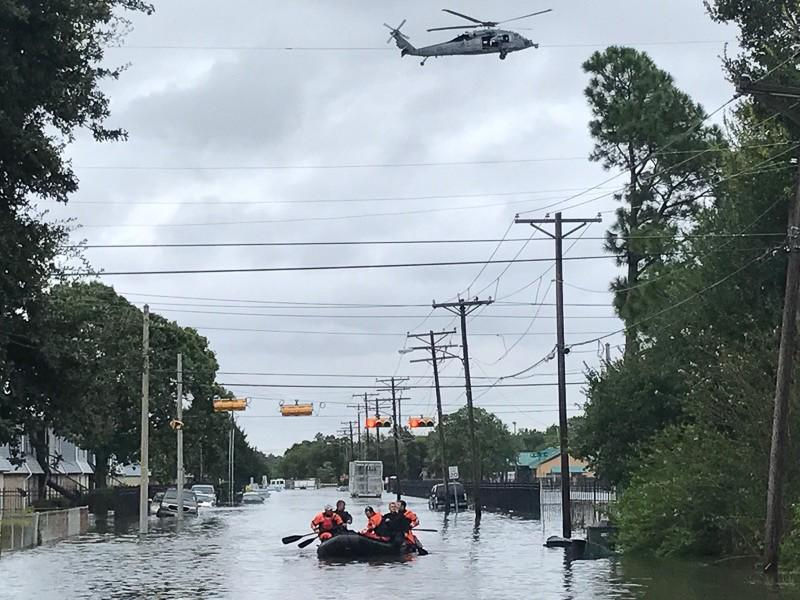 Photo of rescue workers in Port Arthur, Texas, traveling the flooded city by boat and helicopter after Hurricane Harvey in 2017.