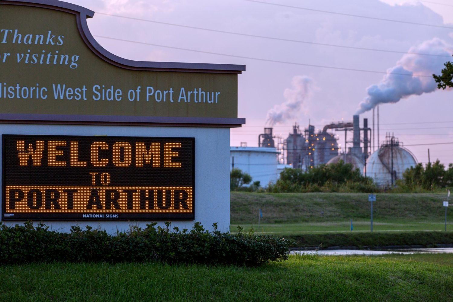 Photo of a sign reading Welcome to Port Arthur with smoke rising from the smokestacks an oil refinery in the background.
