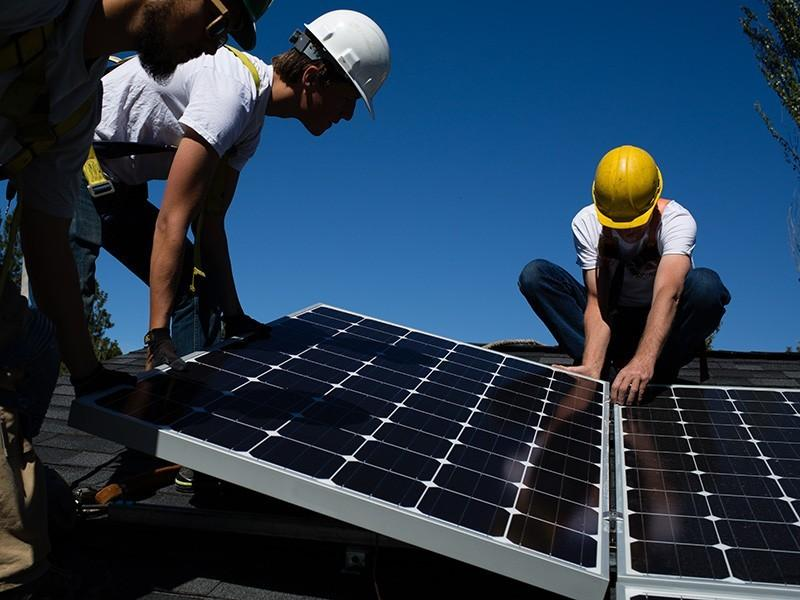 Workers install solar panels.