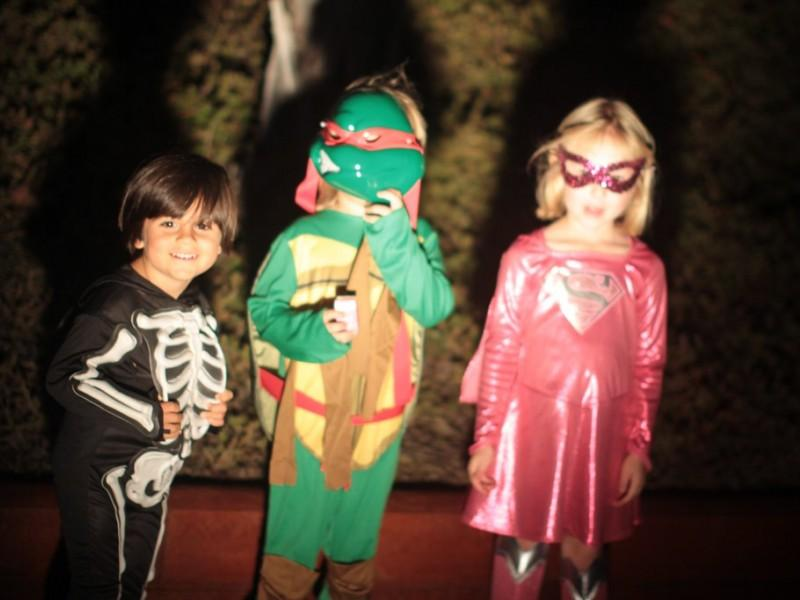 Three children dressed for Halloween in, from left to right, skeleton, Teenage Mutant Ninja Turtles, and Super Girl costumes.