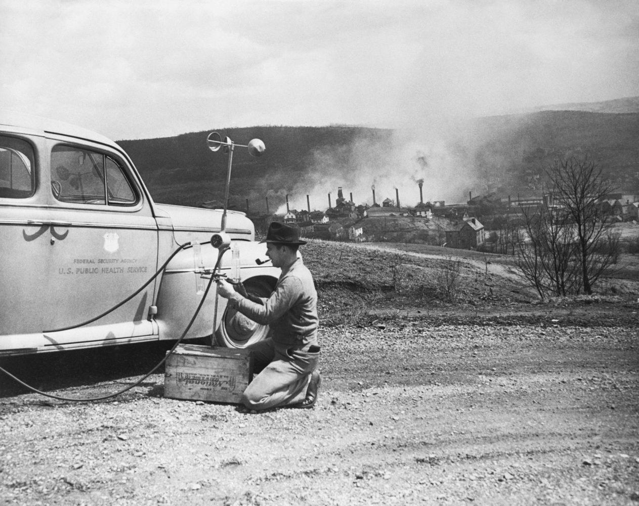 A U.S. Public Health Service worker measures samples of air pollution in Donora, PA.