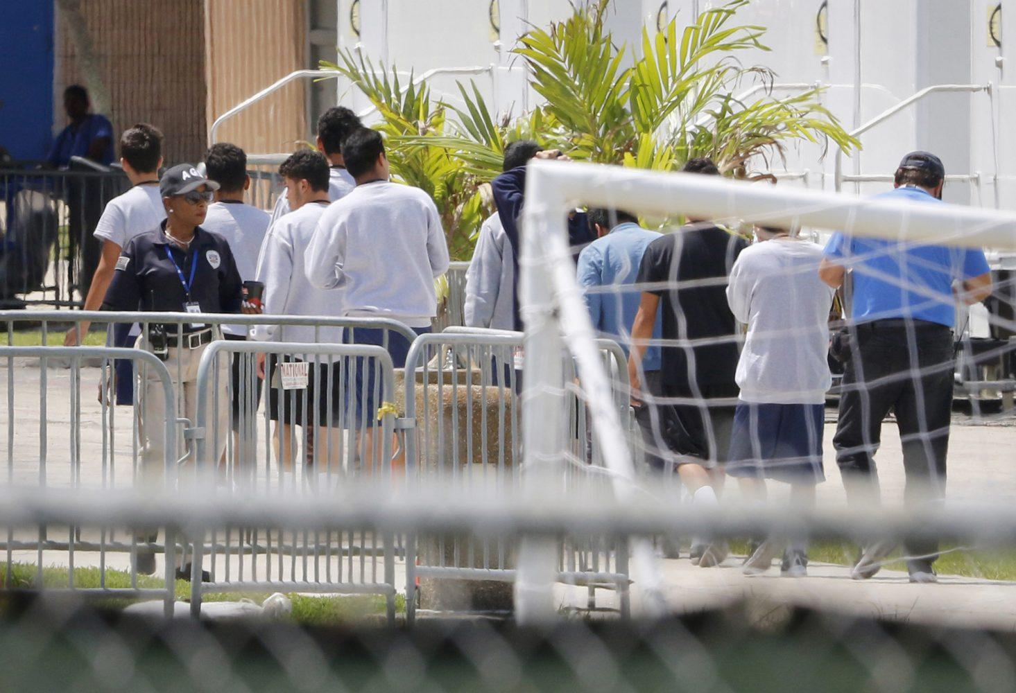 Photo of teenage boys walking in line under the watch of a guard at Homestead Detention Center in 2018.