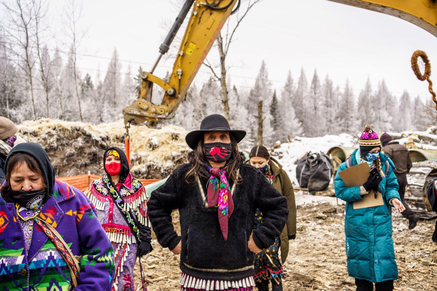 Winona LaDuke, center, and water protectors stand in front of the Line 3 construction site in January.