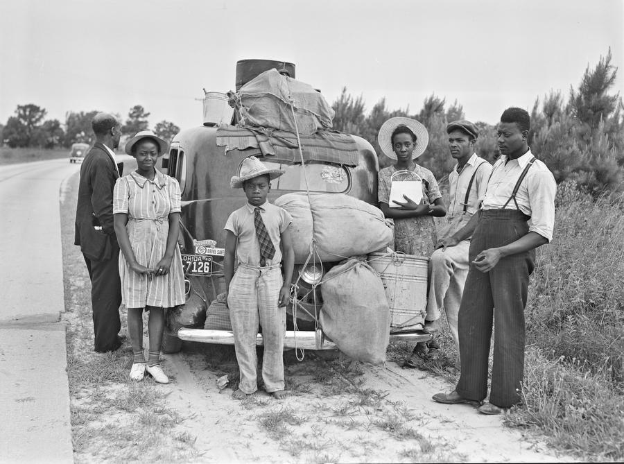 Archival photo of farmworkers from Florida standing by their car on a North Carolina roadside along a drive to work on a New Jersey farm in 1940.