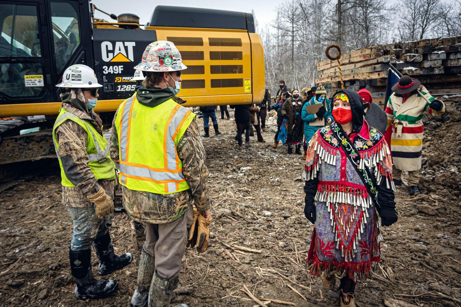 Clad in a traditional jingle dress, Dani Pieratos, a member of the Bois Forte Band of Chippewa, makes eye contact with a construction worker as she exits the construction zone of the Enbridge Line 3 pipeline project.