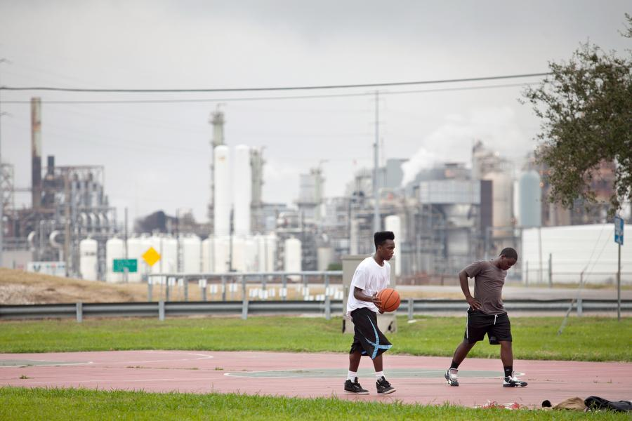 Photo of teenagers playing basketball in the Carver Terrace housing project, where a massive Valero refinery in Port Arthur, TX, looms in the background.