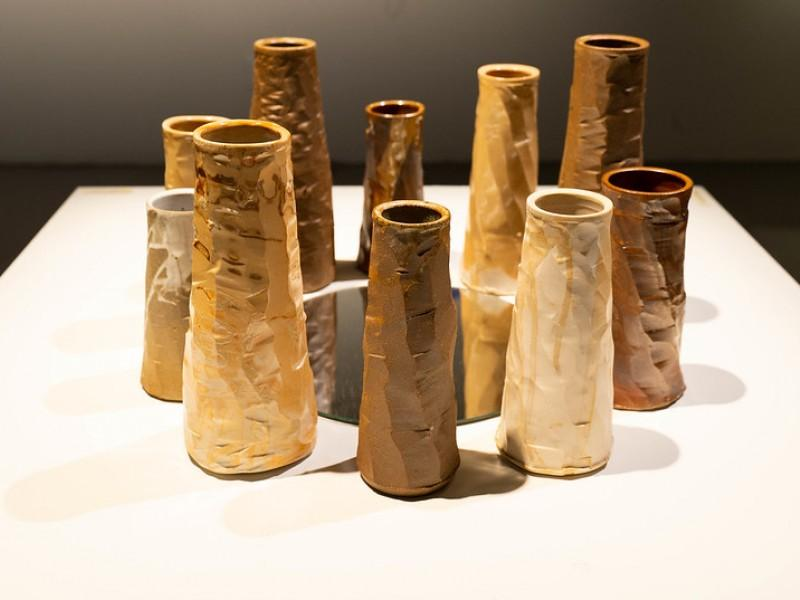 photo of 10 pipe-shaped stoneware and porcelain vessels assembled in the shape of a sacred circle