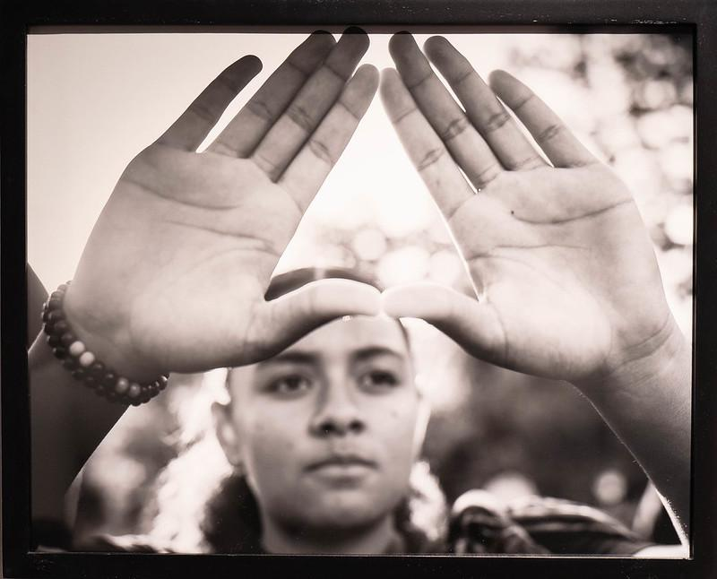 photo of a Hawaiian activist with arms outstretched and hands formed in a triangle signifying the sacred Mauna Kea mountain