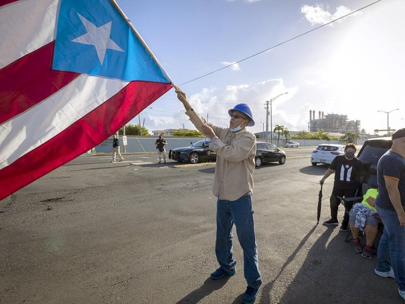 A protester waves the Puerto Rican flag during a public demonstration against the privatization of the island's electricity service