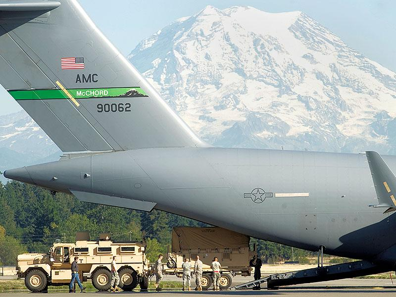 The back of a large aircraft. On the tail is an American flag and the characters McCHORD 90062. A large beige utility vehicle hauling a loaded covered trailer is at the base of the airplane. Multiple people dressed in fatigues are surrounding the trailer. A snowcapped mountain in the background.