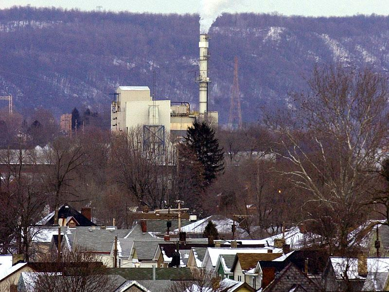 Emissions billowing out of an industrial flume, peeking out amidst trees. In the foreground are residential houses, speckled with snow. In the background is a tree filled hill side.
