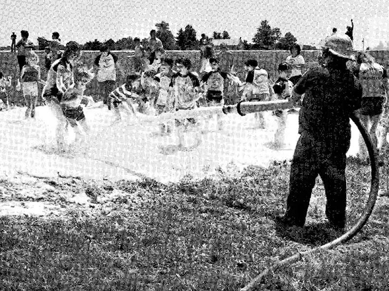 Black and white archival image of a group of youth standing in foam. A person dressed in a helmet and uniform is holding a long hose, spraying foam at the smiling youth.