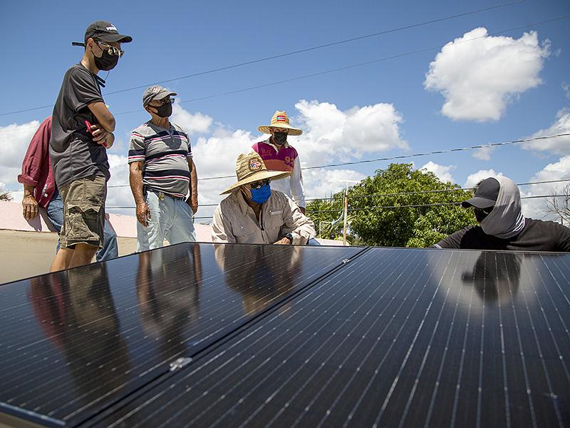 A group of six stand around a set of solar panels. They have sunhats on, sunglasses, and masks. One person with a fabric wrapped around his neck, face, and back of his head is crouched near the back of the panels. Blue skies, wispy clounds, sunny.