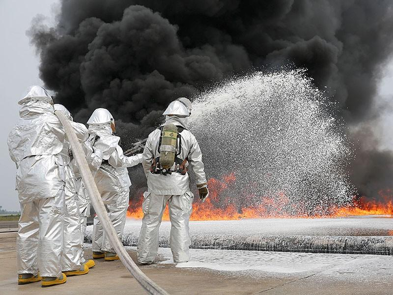 The backside of four marines dressed in silver-colored suits. They spray white foam onto a line of orange and yellow flames. A cloud of black smoke emanates from the flame.