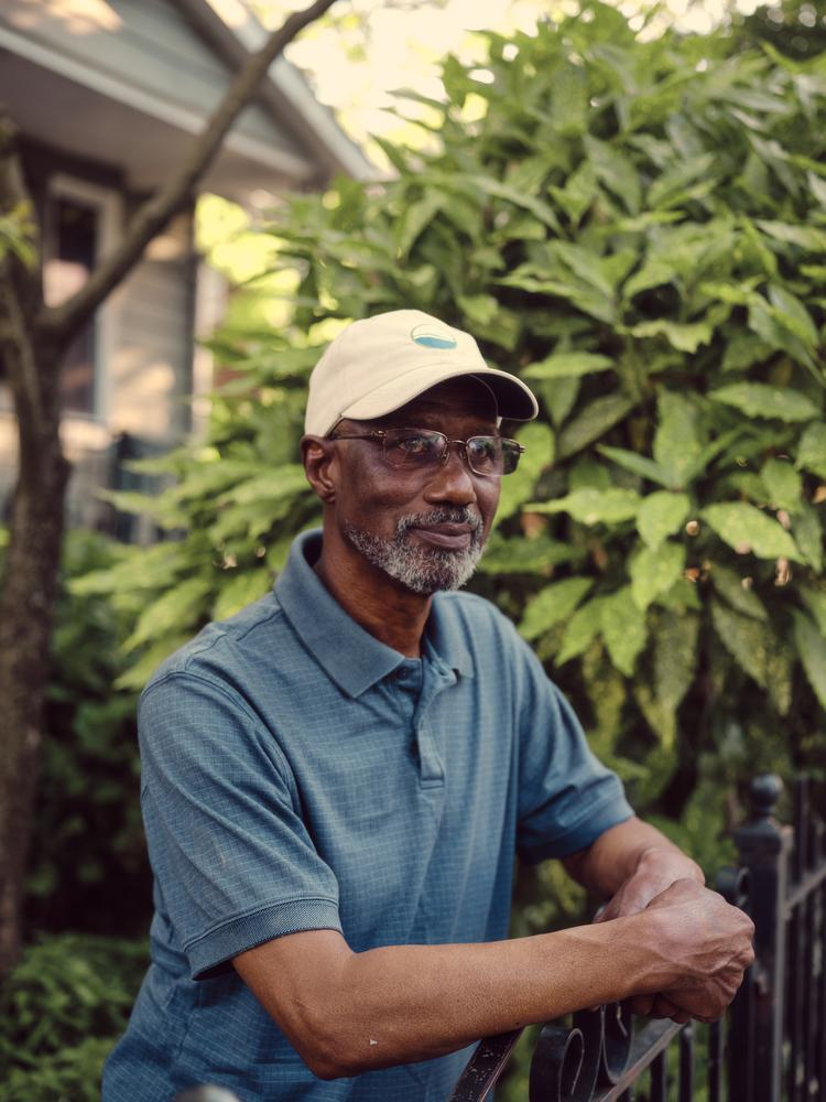 Dennis Chestnut in front of his home in the Eastland Gardens neighborhood in Washington, D.C. He is wearing a light colored cap, glasses, and a blue collared short sleeve shirt. His hand rests on the metal fencing. Behind him is greenery in front of a house.