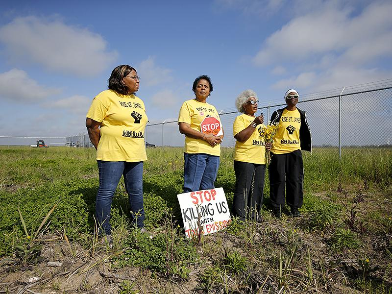 Four Members of RISE St. James stand in a field. They are wearing yellow tee shirts with the words Rise St. Jame, and a graphic of a raised printed in the front. There is a sign on the floor braced against the legs of Sharon Lavigne, who is second from the left. The sign reads stop killing us with toxic emissions. Sharon is holding a red octagonal stop sign. Gail LeBoeuf, third from the left, is holding a bouquet of yellow flowers in their left hand and another small object in their other hand.