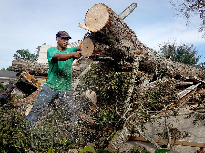 Workers remove a tree that fell on a home during Hurricane Ida on August 31, 2021, in Houma, Louisiana.