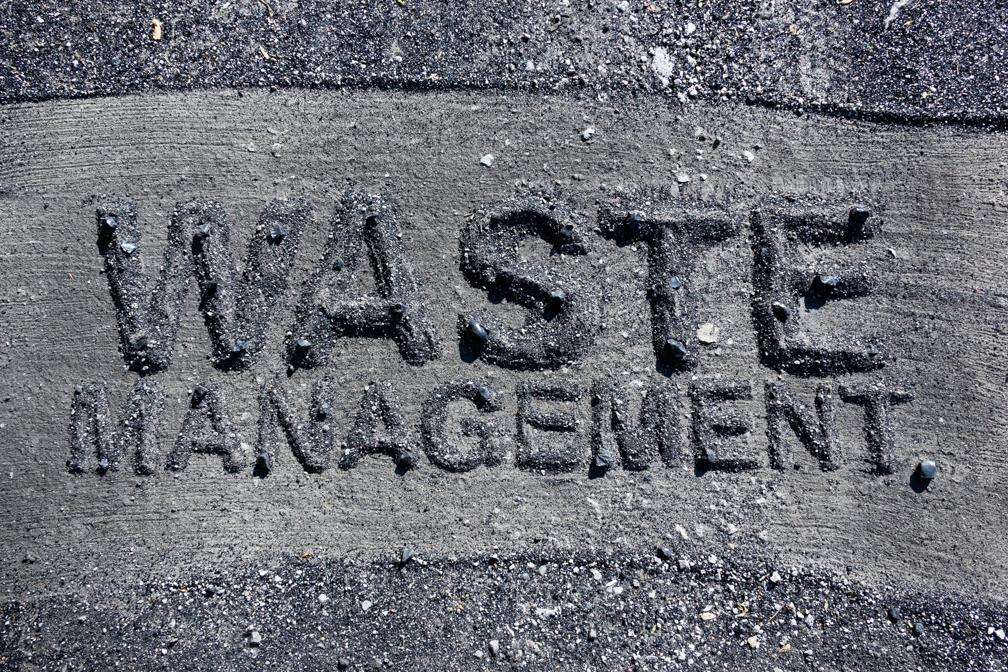 Waste Management, coal ash lettering on coal ash covered roadbed in Pines, Indiana, 2016.